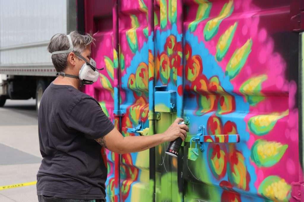 Mural artist, Monica Mickeler, spray painting a public art piece